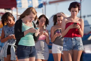 Young-women-using-smartphones-at-an-amusement-park